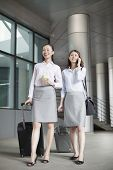 Two young businesswomen walking with suitcases and talking