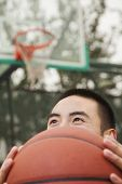 Young man covering his face with basketball