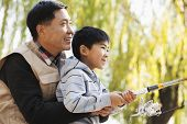 stock photo of weeping  - Father and son fishing together at lake - JPG