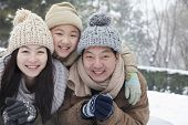 stock photo of cold-shoulder  - Family laying in snow for portrait - JPG