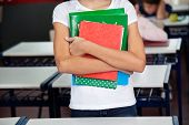 Midsection of schoolgirl holding books while standing in classroom