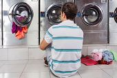 stock photo of laundromat  - Rear view of young man sitting on floor in front of washing machines at laundromat - JPG