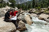 image of himachal pradesh  - Hiker trekkers read a trekking map on trek in Himalayas mountains - JPG