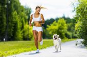 picture of dog park  - Young attractive sport girl running with dog in park - JPG