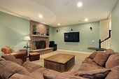 stock photo of basement  - Lower level basement with stone fireplace and large screen TV - JPG