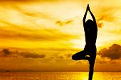 Woman doing yoga at sunset time
