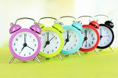 Colorful alarm clocks on table on light background