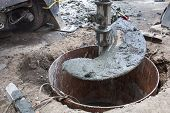 stock photo of auger  - A large auger bores a hole in the street to install a traffic light - JPG