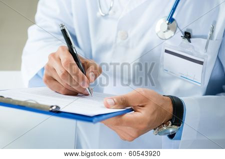 Close-up Of Male Doctor Filling The Medical Form poster