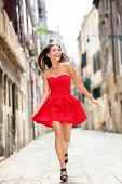 Happy beautiful woman in red summer dress walking and running joyful and cheerful smiling in Venice, Italy. Pretty sexy fashion model girl in her 20s. Mixed race Asian Caucasian female model outside.
