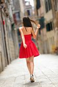 Woman in red dress walking in street in Venice, Italy cheerful and happy in rear view showing back o