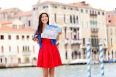 Travel tourist woman with camera and map in Venice, Italy. Asian girl on vacation smiling happy by G