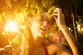 Women in vineyard with glass of red wine and grapes in sunflare