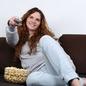 Young Woman Watching Tv And Eating Popcorn