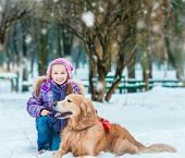 beautiful little girl sit with her dog on the snow in winter