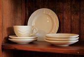 White glazed stoneware on warm-tone wood shelf