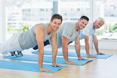 Portrait of happy fit men doing push ups at gym