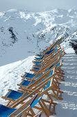 Deckchairs on peak In Alps In Winter