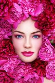 Portrait of young beautiful blue-eyed woman with pink peonies around her face