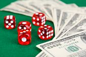 Red dices and dollars on green background