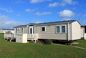 Side view of cream colored caravans in modern trailer park, England.