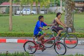 Grandmother And Grandson Riding Bicycle In Park