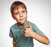 blonde boy kid in blue shirt holding thumbs up, showing sign yes