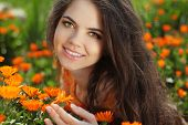 Happy Smiling Girl. Beautiful Romantic Brunette Female Outdoors Portrait. Over Marigold Flowers Fiel