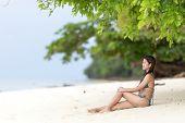 Beautiful Filipina woman sitting in her bikini on a tropical beach in her bikini on the golden sand