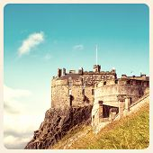A view of Edinburgh Castle, an historic fortress perched on Castle Rock, Scotland. Filtered to look like an aged instant photo.