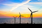 image of wind-vane  - Wind power and colorful sunset over the sea - JPG