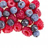 Raspberries and blueberries heap pile isolated on white  background