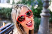 pic of pinup girl  - Funny girl with red heart glasses in a park - JPG