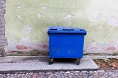 Blue Dumpster Against A Bright Green Wall