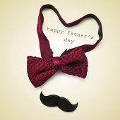 a bow tie forming a heart, a mustache and the sentence happy fathers day in a beige background, with