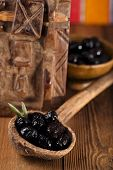 black marinated Olives in old spoon with moroccan  ornament on wood, shallow dof