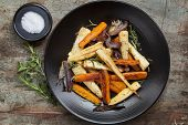 Roasted root vegetables on a black serving platter.  Carrots, parsnips, turnips, red onions, salt, and herbs.  Overhead view.