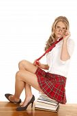 foto of short skirt  - A woman with glasses sitting on a stack of books short skirt - JPG
