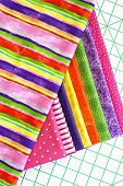 Stack of woven cotton fabric in bright colors on sewing cutting board.  Swatches in coordinated colors for quilting, crafts, or home decor sewing projects.  Closeup taken from above.