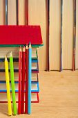 Pile Of Books And Colored Pencils On A Wooden Surface Against The Background Of A Number Of Books.