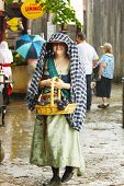 MUSKOGEE, OK - MAY 24: A woman dressed in historical costume enjoys rainy weather at the Oklahoma 19