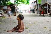 naked poor kid sitting in the middle of the road