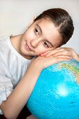 Dreaming About Holidays. Thoughtful Smiling Girl With Blue Round Globe
