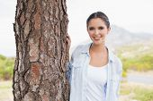 Portrait of a smiling young woman standing by tree trunk