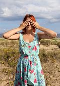 Redhead Girl Covering Her Eyes With Hands At The Seashore