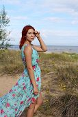 Redhead Girl In Long Dress Standing At The Seashore