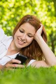 Pretty redhead lying on the grass sending a text on a sunny day