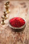 saffron spice in antique vintage iron bowls weights stacked on wooden table