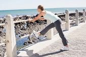 Fit mature woman warming up on the pier on a sunny day
