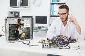 Computer engineer looking at broken device and making a phone call in his office